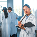 A female lab professional looking at the camera holds a notebook in her arm. In the background other lab professionals with their backs to the camera confer.