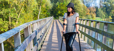 A woman standing with elbow crutches on a bridge as she looks into the distance