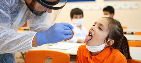 Pediatrician taking saliva test from children with face masks in a school