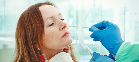 A woman with a mask around her neck is having a swab inserted into her nose by a healthcare provider with gloved hands
