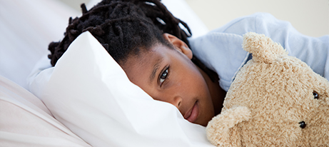A young girl laying down with half her face obscured by a pillow and holding a teddy bear looks straight ahead